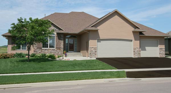 house with healthy grass, driveway seal and landscaping